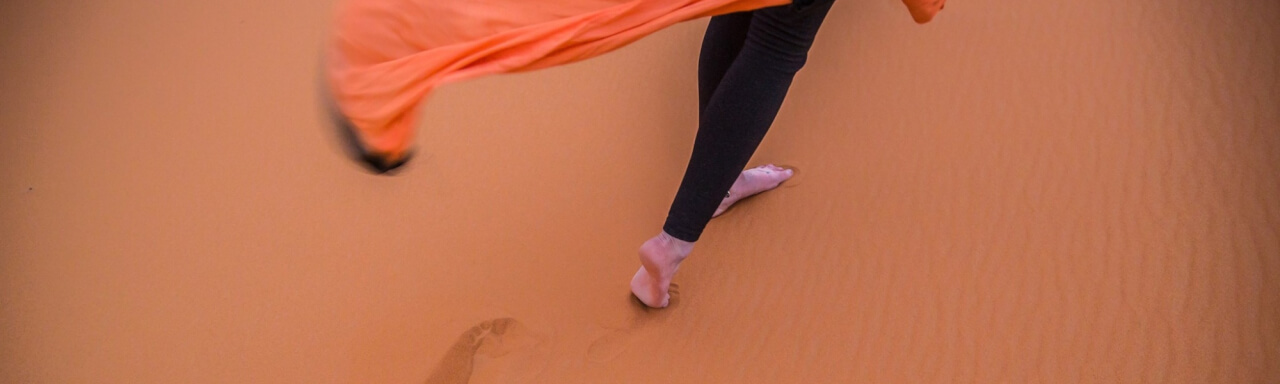 Feet walking on desert sand with flowing tunic